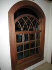 shaped wood window with intricate grill pattern